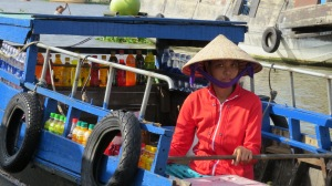 A lady selling drinks to stall holders at the Floating Market. Can Tho.