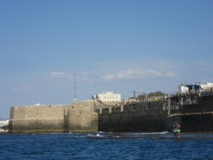 City walls from the sea, with fisherfolk.
